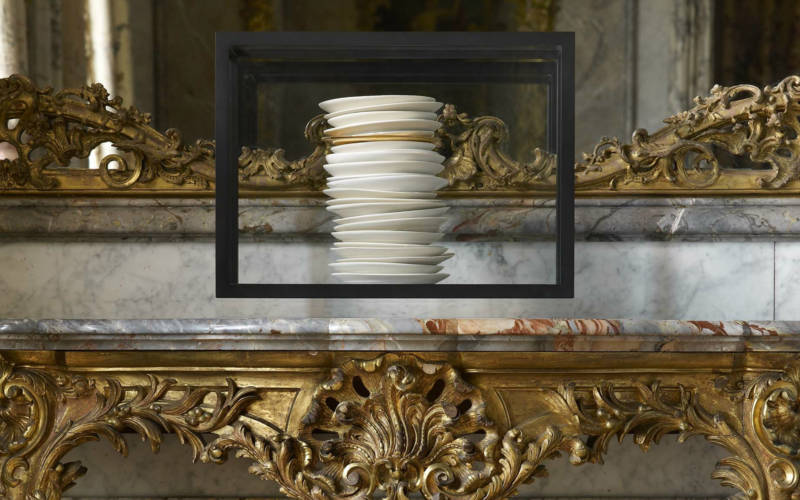 a stack of white porcelain plates by Edmund du Waal on an 18th century French side table