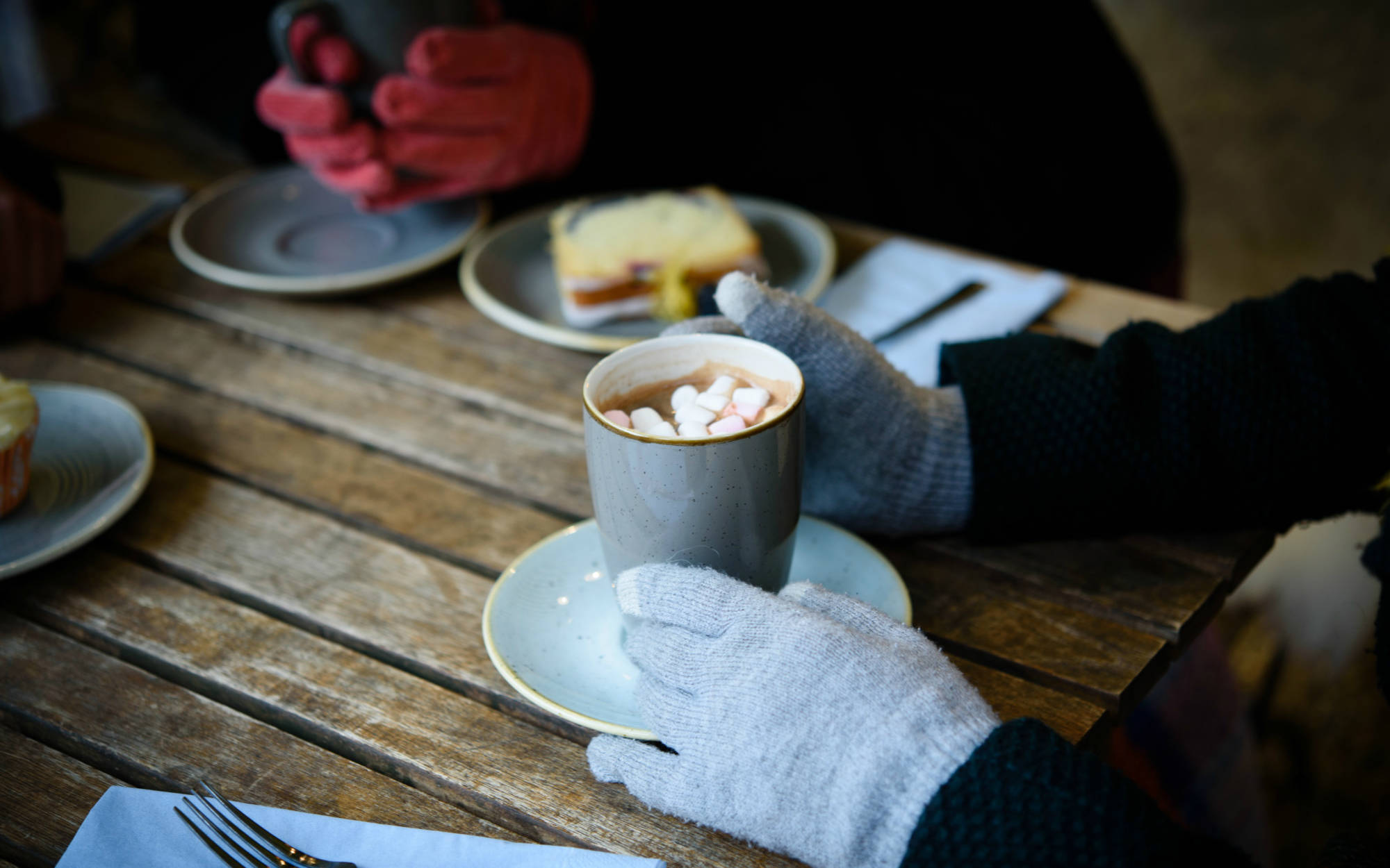 Gloved hands clasp steaming hot chocolate