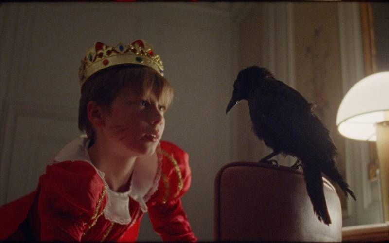 Boy wearing a crown faces a crow in a bedroom at Waddesdon Manor