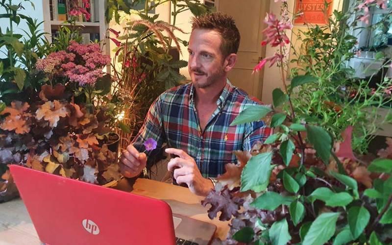 Gardener Nick Bailey sat among house plants